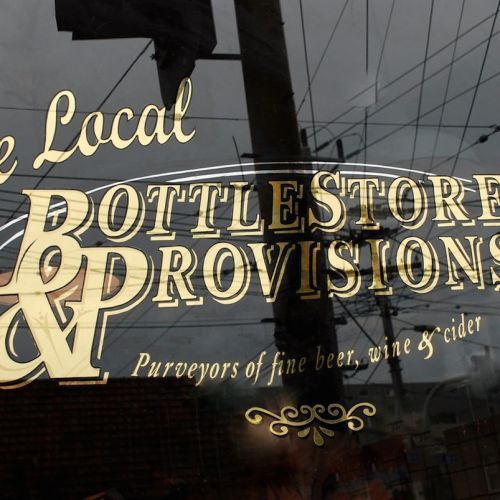 on glass gold leaf gilded window signwriting the local bottlestore and provisions